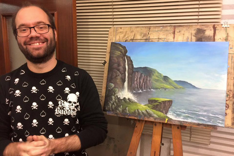 Image of a smiling Ruben Megido in front of one of his oil paintings
